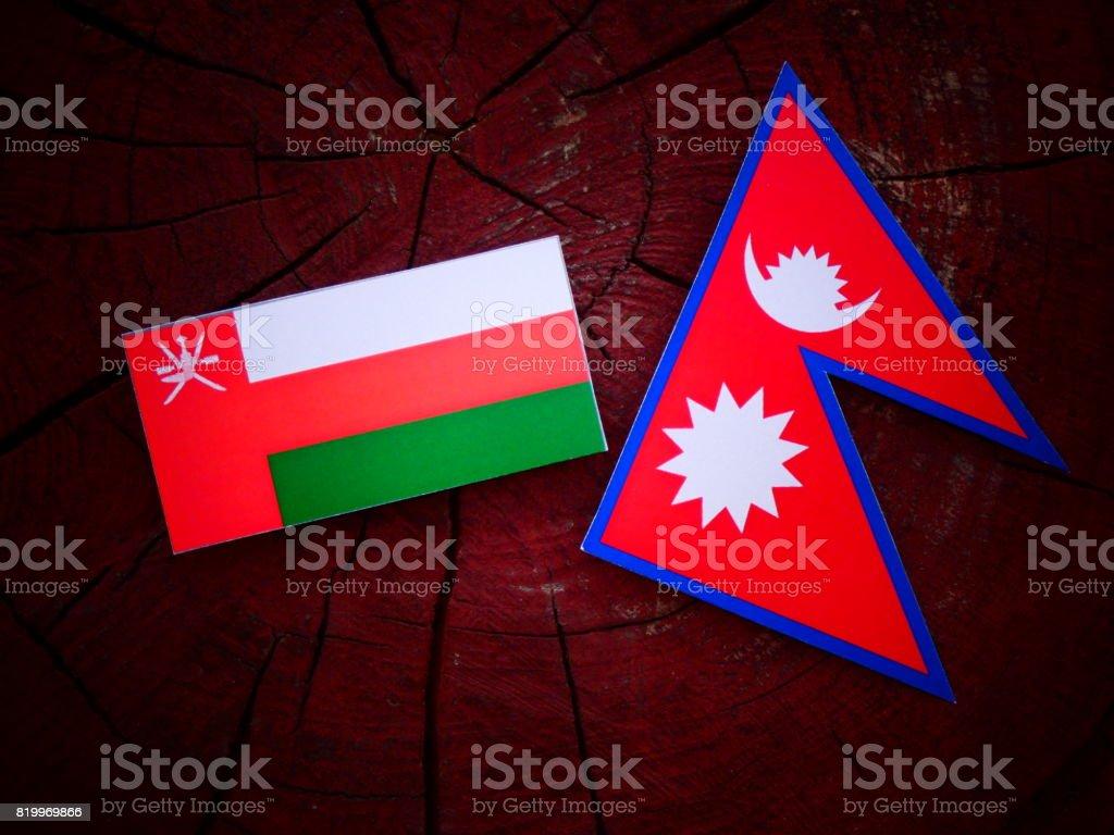 Omani flag with Nepali flag on a tree stump isolated stock photo