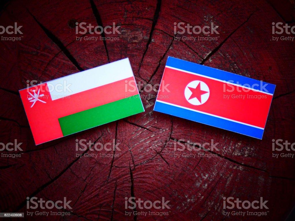 Omani flag with North Korean flag on a tree stump isolated stock photo