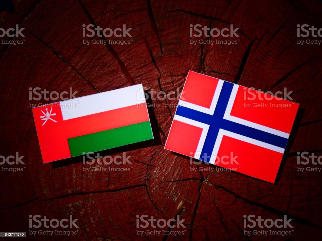 Omani flag with Norwegian flag on a tree stump isolated stock photo