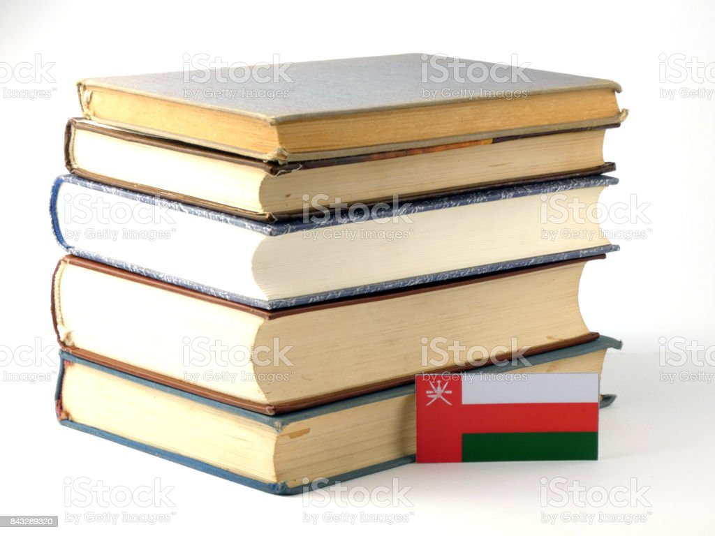 Omani flag with pile of books isolated on white background stock photo