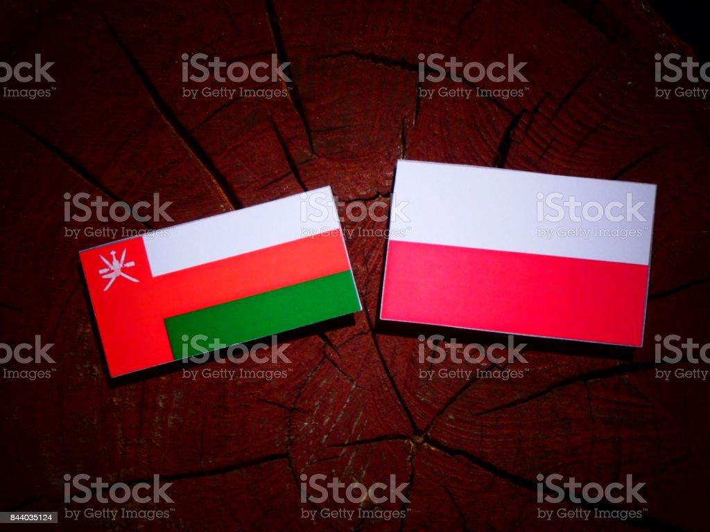 Omani flag with Polish flag on a tree stump isolated stock photo