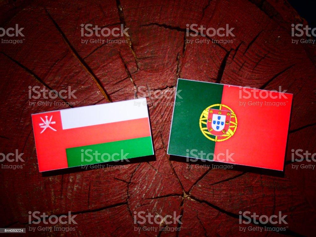 Omani flag with Portuguese flag on a tree stump isolated stock photo
