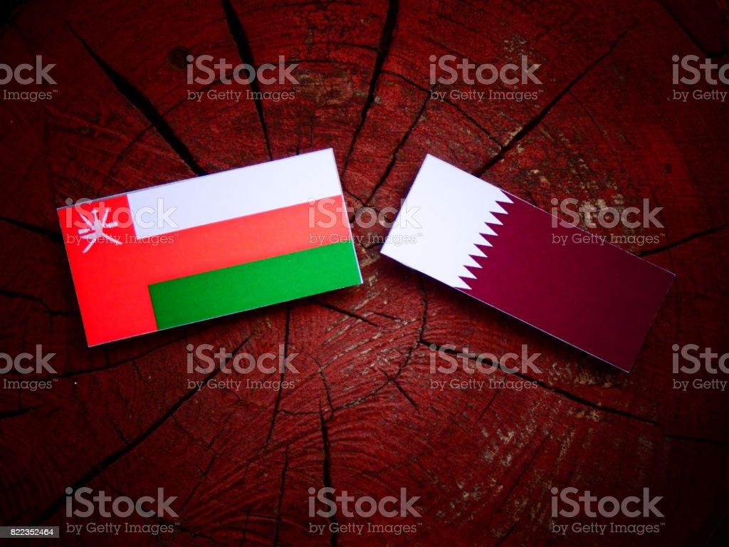 Omani flag with Qatari flag on a tree stump isolated stock photo