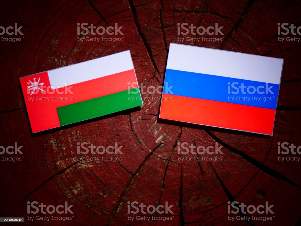 Omani flag with Russian flag on a tree stump isolated stock photo
