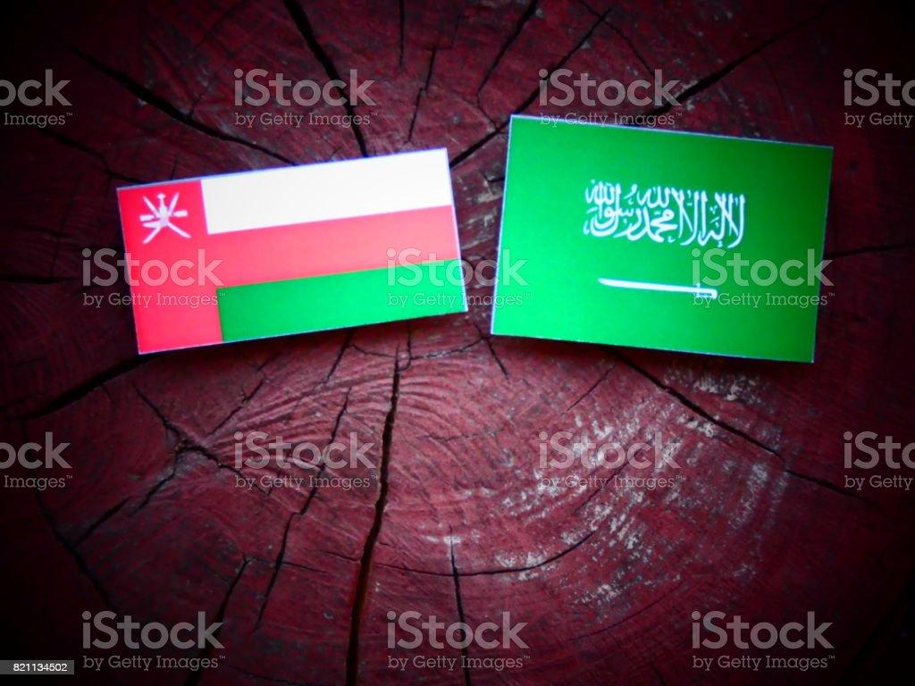 Omani flag with Saudi Arabian flag on a tree stump isolated stock photo
