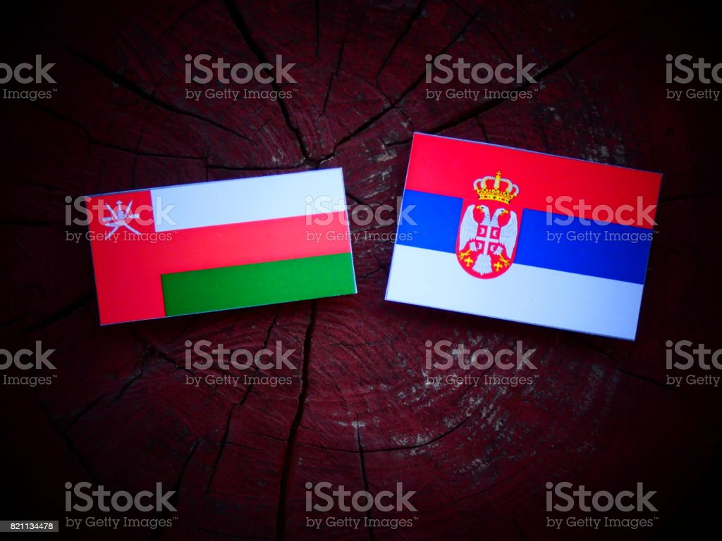 Omani flag with Serbian flag on a tree stump isolated stock photo