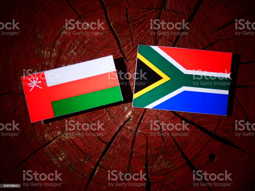 Omani flag with South African flag on a tree stump isolated stock photo