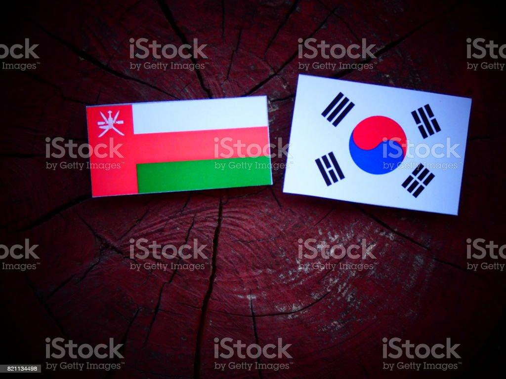 Omani flag with South Korean flag on a tree stump isolated stock photo