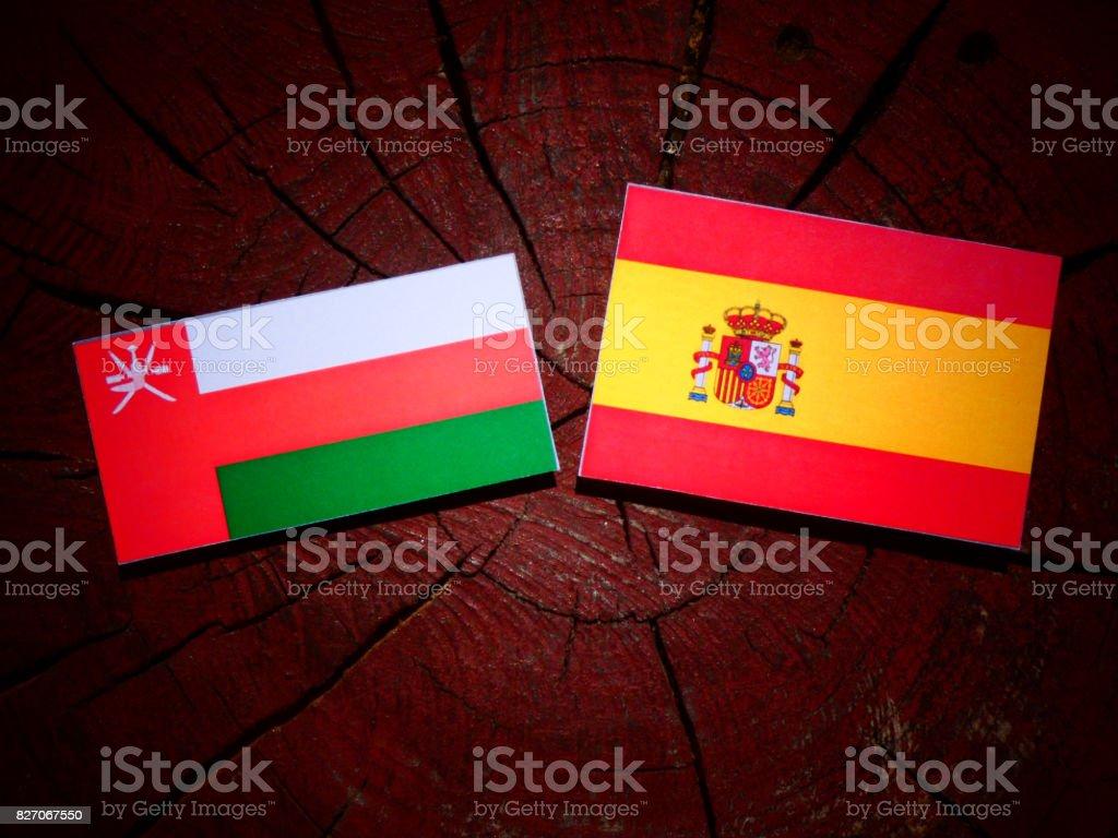 Omani flag with Spanish flag on a tree stump isolated stock photo