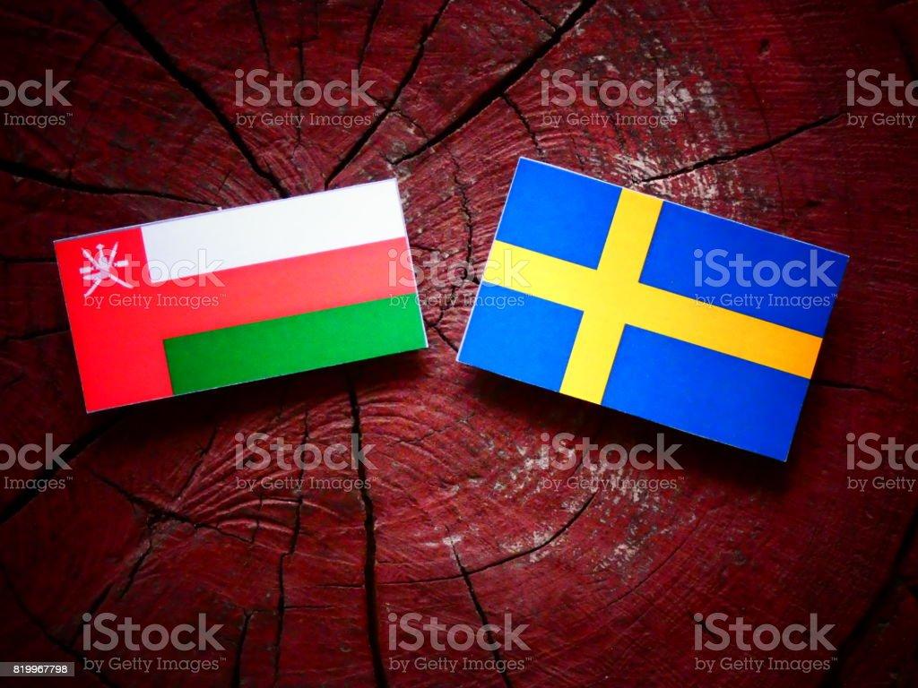 Omani flag with Swedish flag on a tree stump isolated stock photo