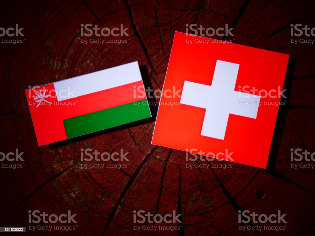 Omani flag with Swiss flag on a tree stump isolated stock photo