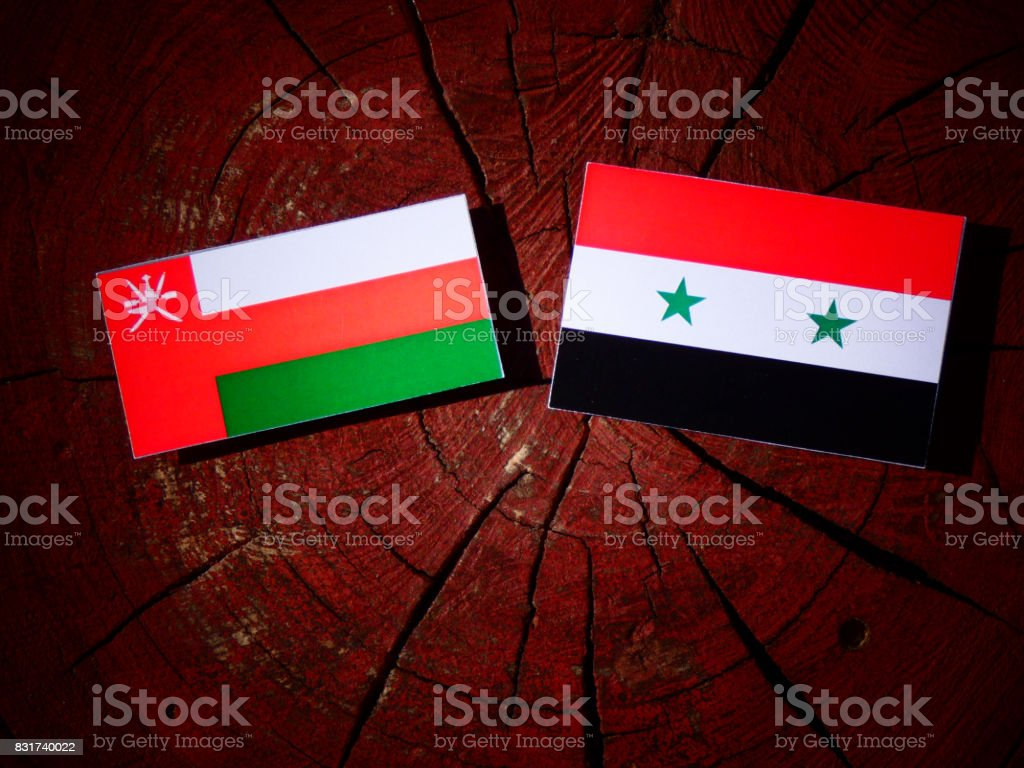Omani flag with Syrian flag on a tree stump isolated stock photo
