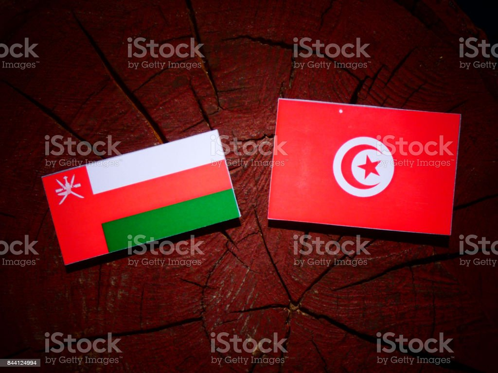 Omani flag with Tunisian flag on a tree stump isolated stock photo