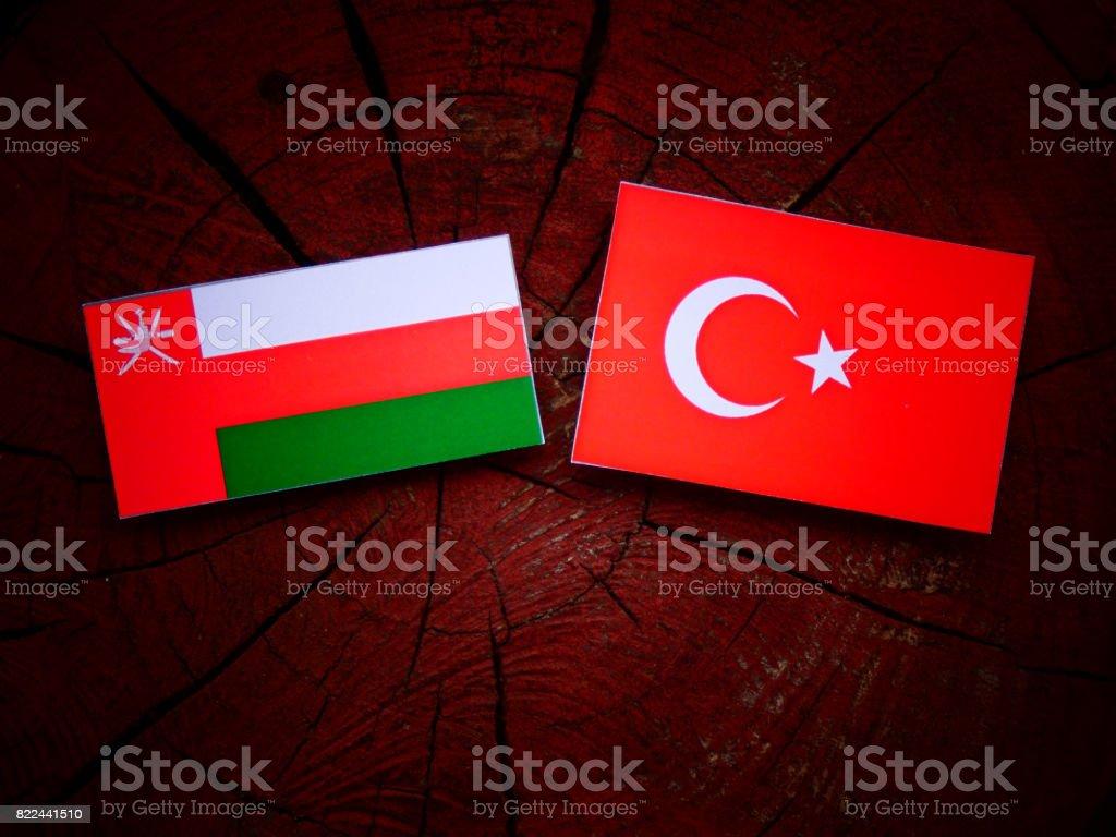 Omani flag with Turkish flag on a tree stump isolated stock photo