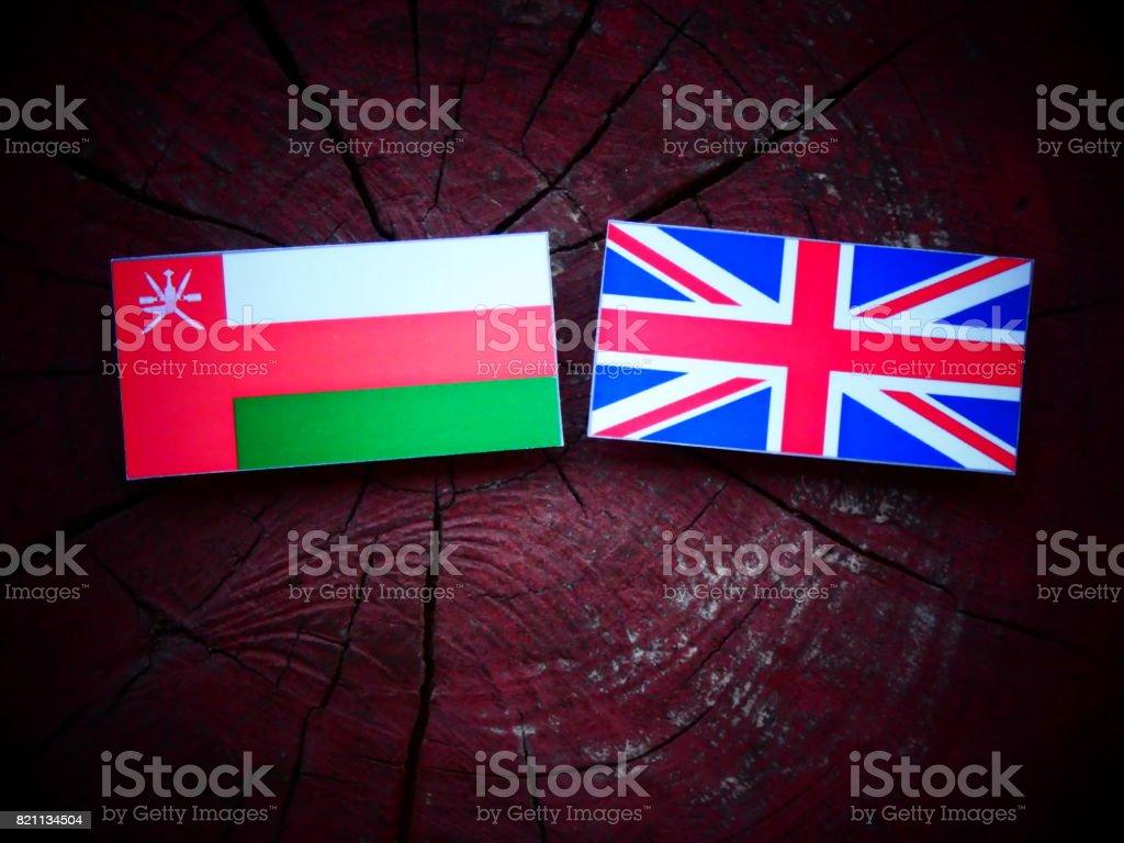Omani flag with UK flag on a tree stump isolated stock photo