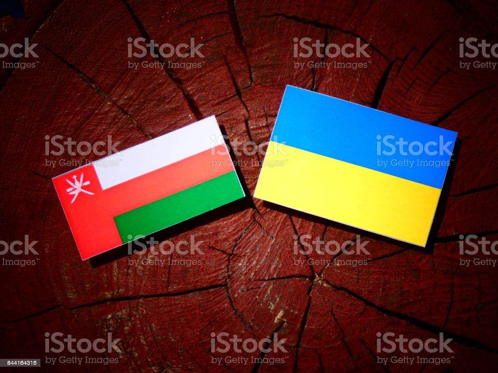 Omani flag with Ukrainian flag on a tree stump isolated stock photo