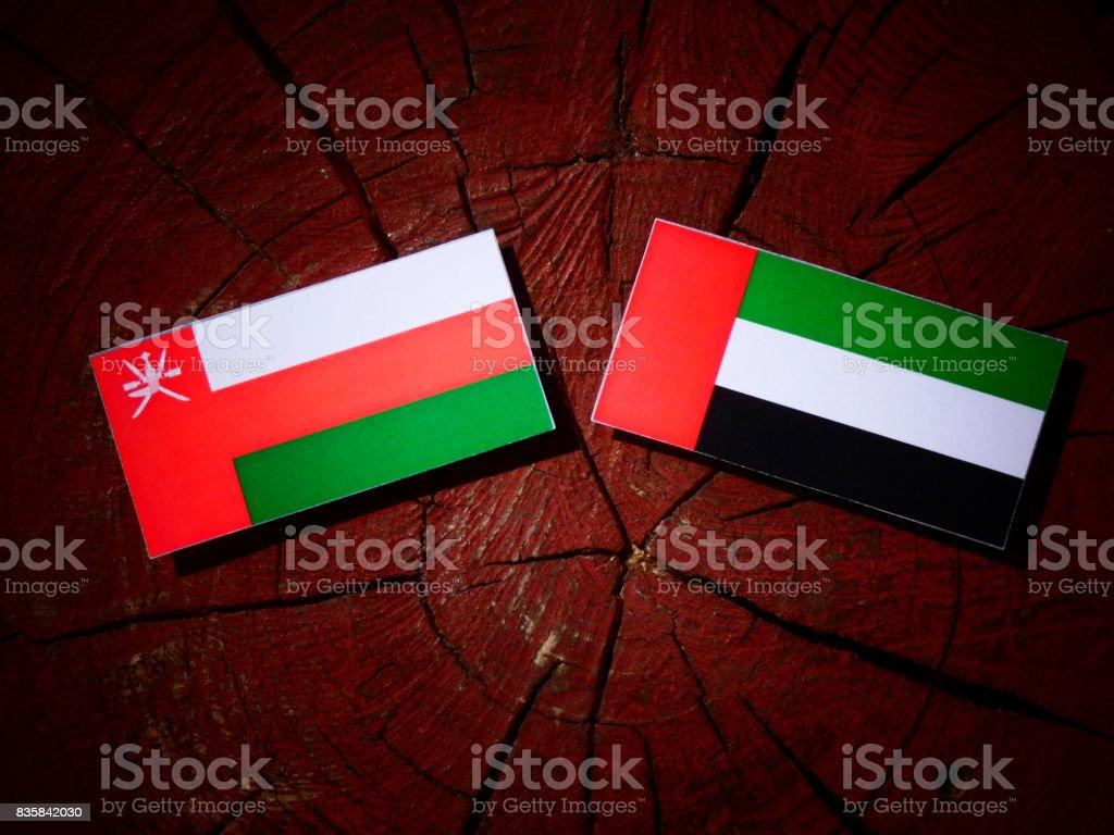 Omani flag with United Arab Emirates flag on a tree stump isolated stock photo