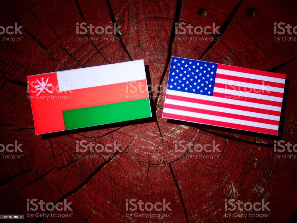 Omani flag with USA flag on a tree stump isolated stock photo