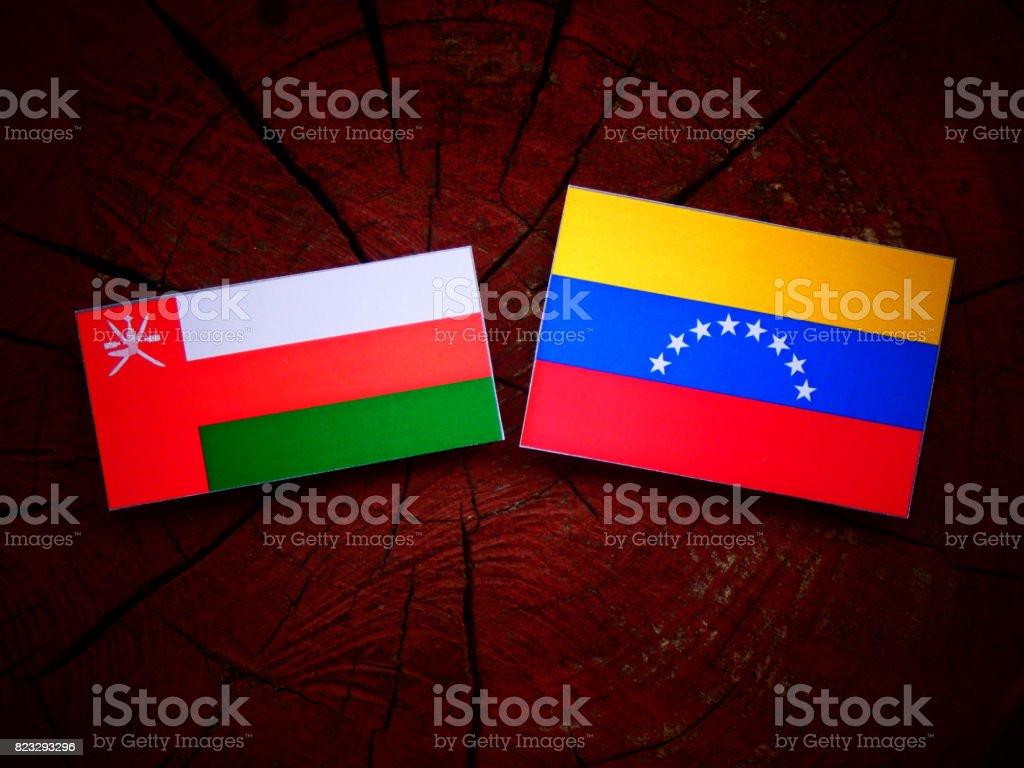 Omani flag with Venezuelan flag on a tree stump isolated stock photo