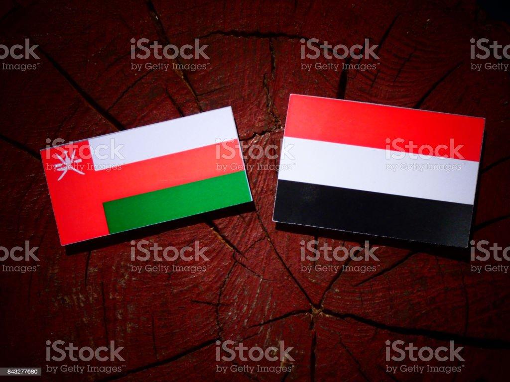 Omani flag with Yemeni flag on a tree stump isolated stock photo