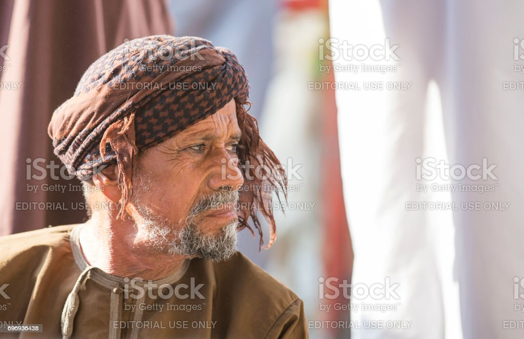 Omani man in traditional clothing, at Nizwa goat market, looking at a goats passing stock photo