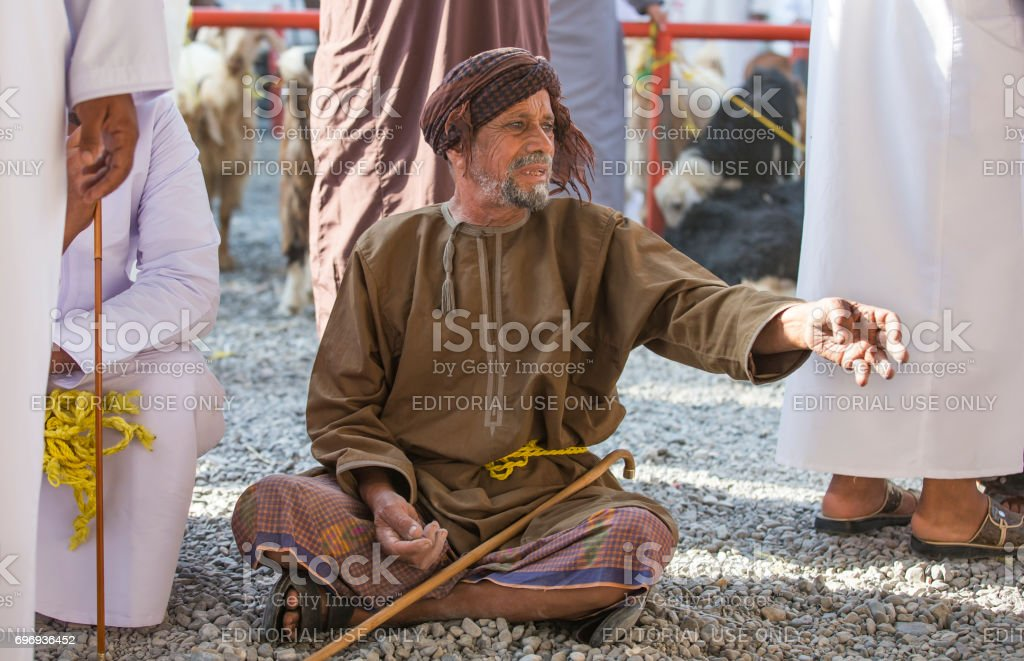 Omani man in traditional clothing at Nizwa goat market, trying to get attention of a salesman passing by stock photo