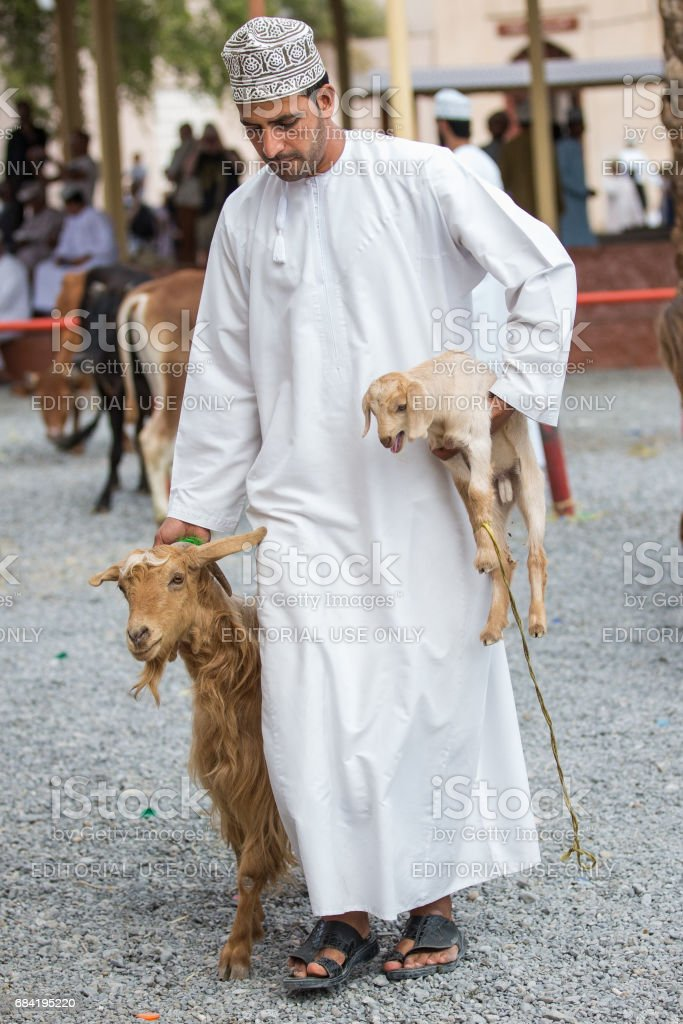 omani man in traditional clothing with a goat at a market stock photo