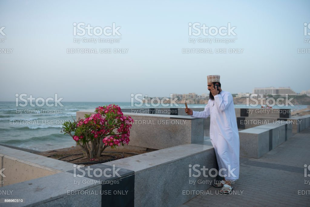 Omani man photographing blossoms with mobile phone stock photo