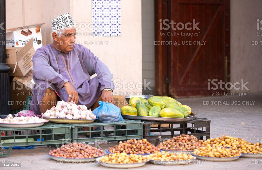 omani man selling new season dates at a street market in Nizwa stock photo