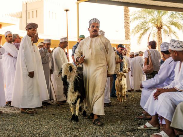 Omani Mann zeigt ein Schaf zur Versteigerung auf dem Nizwa-Tiermarkt – Foto