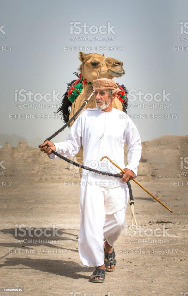omani man walking with his camel stock photo