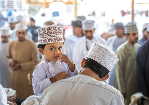 omani man with his son at a market stock photo