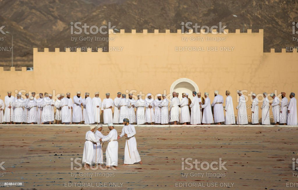 omani men in traditional clothing socialising after a morning prayer at outdoor mosque in Nizwa stock photo