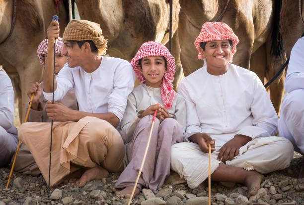 omani men with their camels in a countryside - oman стоковые фото и изображения