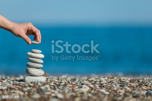 istock oman's hand balancing stacking stones on a beach 933101066