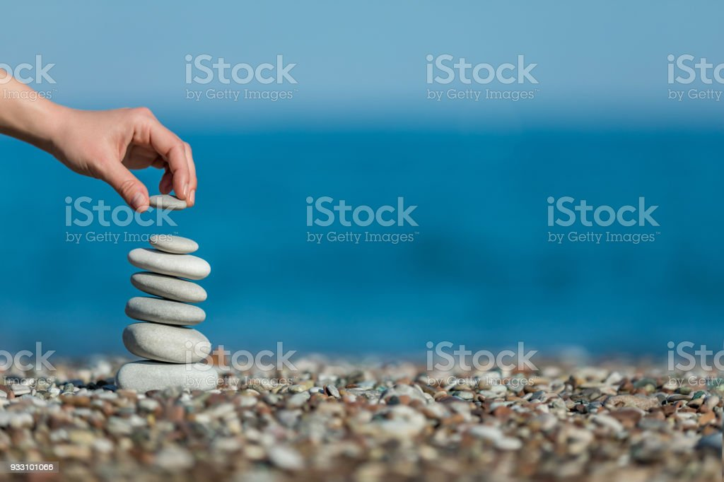 oman's hand balancing stacking stones on a beach stock photo