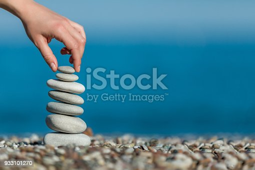 istock oman's hand balancing stacking stones on a beach 933101270