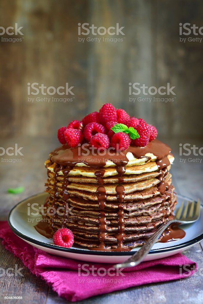 Ombre chocolate pancakes with fresh raspberry and chocolate sauce. stock photo