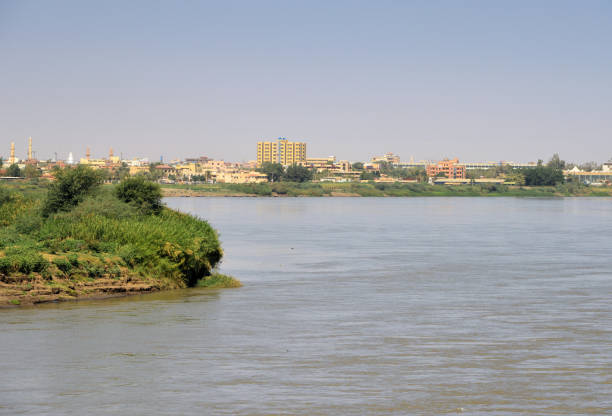 Omdurman skyline and the Nile River near Tuti Island where the Blue and White Nile meet, Khartoum, Sudan Omdurman, Khartoum, Sudan: Omdurman skyline and the Nile River - view of the old capital from the White Nile Bridge - mosque and Mahdi mausoleum on the left omdurman stock pictures, royalty-free photos & images