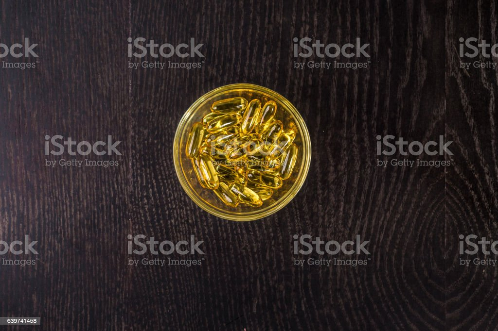 Omega 3 gel capsules in a glass, of fish oil stock photo