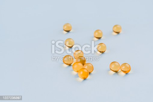 Healthy Omega 3 gel capsules on blue background. Fish oil pills.
