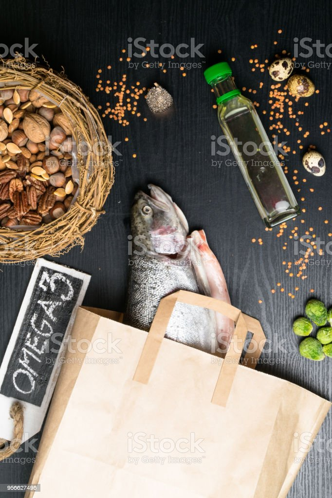 Omega 3 source. Healthy fat salmon or trout, oil, nuts, seeds, chia, lentils, brussels sprouts, eggs stock photo