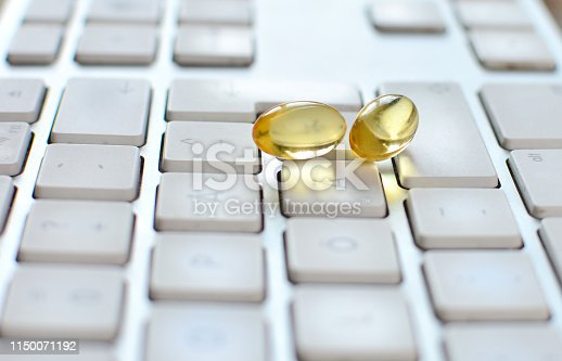 istock Omega 3 vitamin capsules are on the keyboard. 1150071192