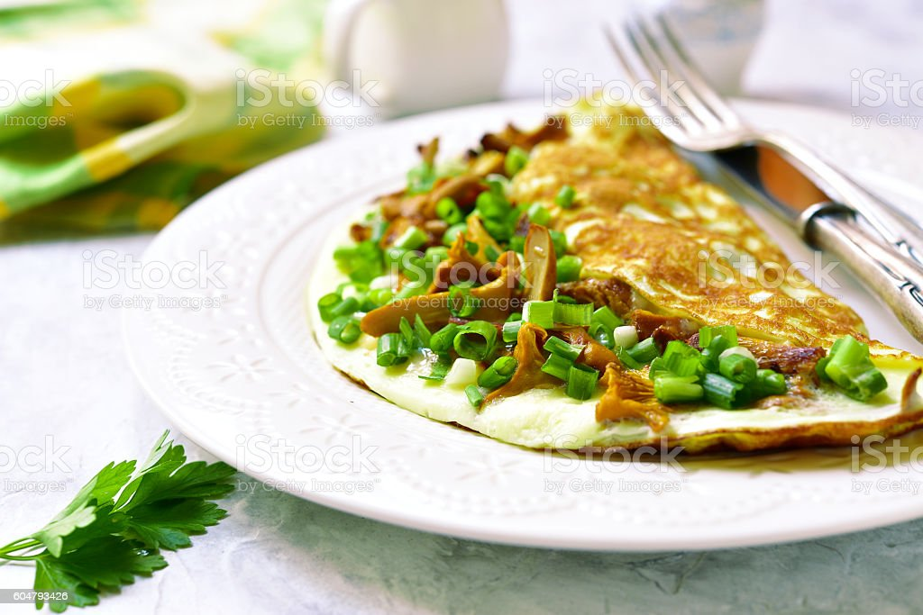 Omelet stuffed with chanterelle mushrooms and cheese. stock photo