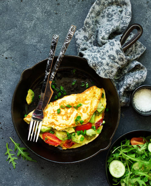 omelet with avocado, tomatoes and cheese for breakfast. stock photo