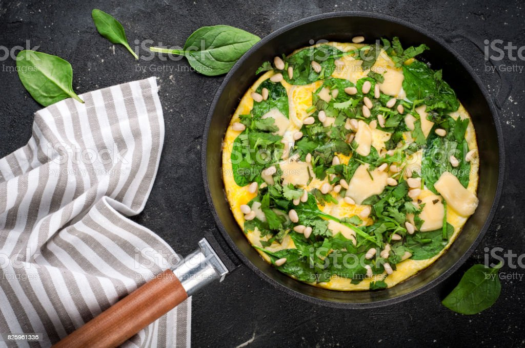 Omelet with eggs, spinach, pine nuts and vegetables. Spinach tortilla in pan on dark background.  Delicious breakfast or appetizer snack stock photo