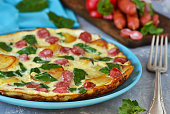 Omelet with spinach, cheese and Bavarian sausages on a concrete background