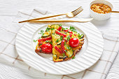 frittata, omelet with zucchini, thin smoked sausages and tomatoes filling on a white plate on wooden table with mustard at the background, horizontal view from above