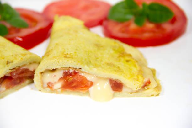 omelett mit geschlagenen eiern gefüllt mit zwiebel-käse und tomaten auf weißem hintergrund mit tomatenscheiben und basilikum gemacht - kräuterfaltenbrot stock-fotos und bilder