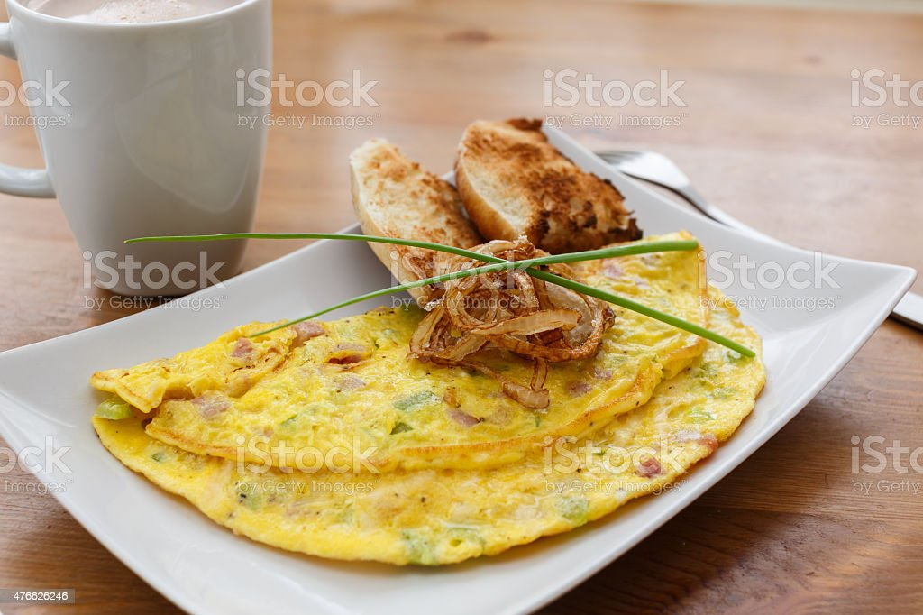 Omelette with bellpepper, ham, cheese and fried onion stock photo